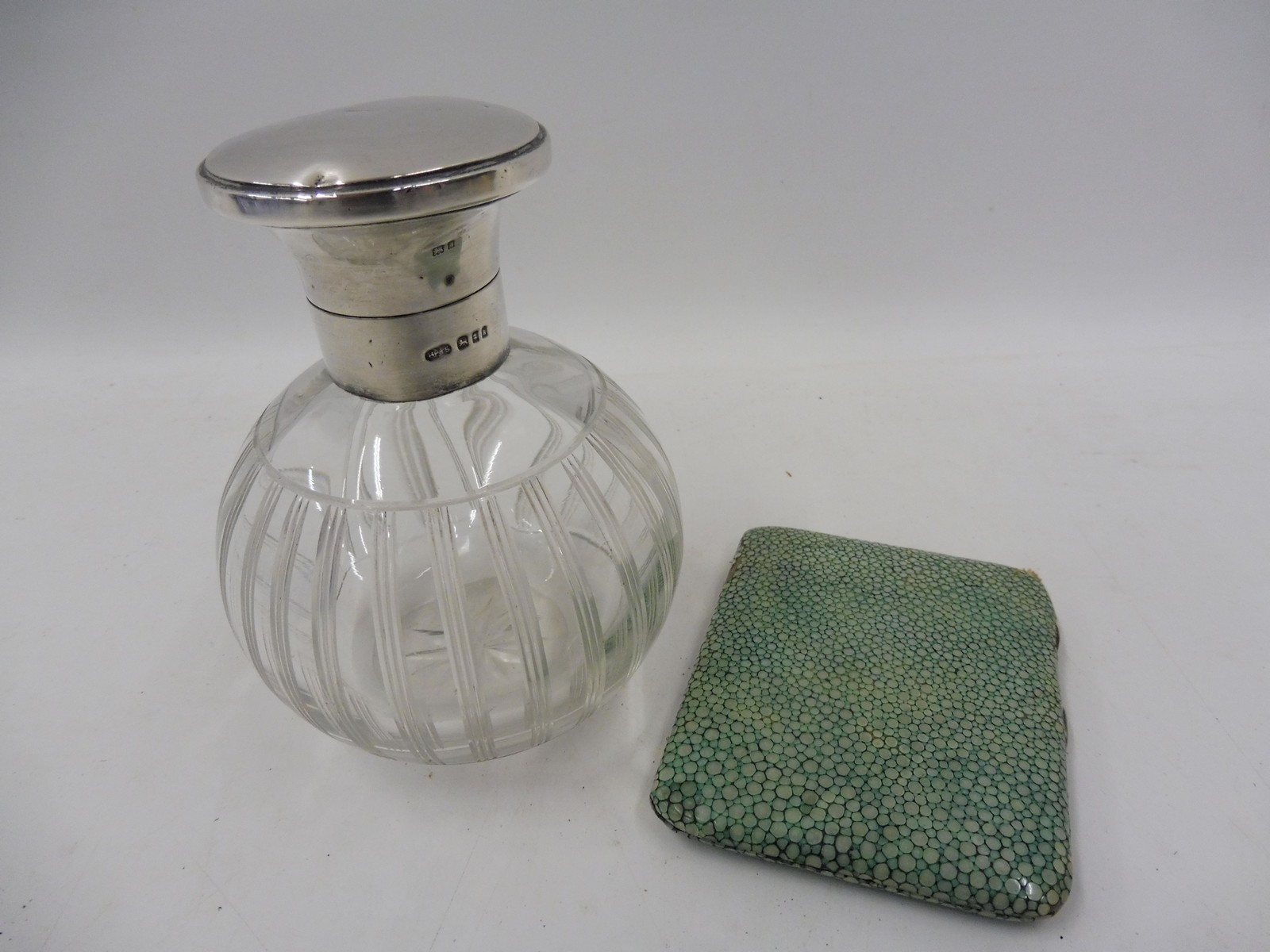 Lot 43 - A silver mounted bulbous glass scent bottle and a shagreen covered silver cigarette case.