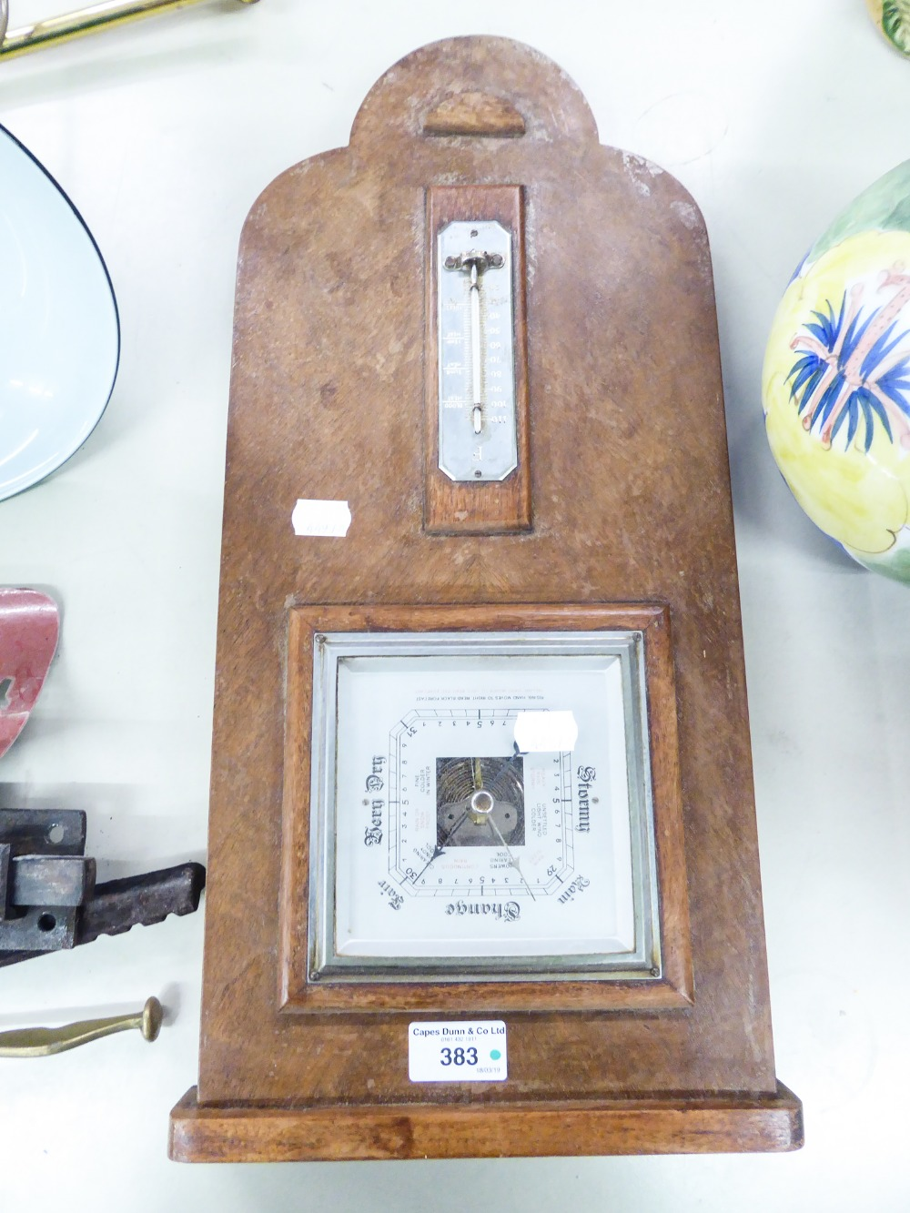 Lot 383 - AN ANEROID BAROMETER AND THERMOMETER IN WALNUT PANEL