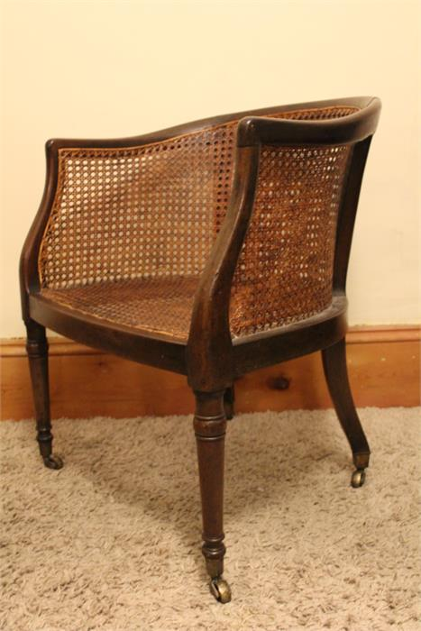 Lot 40 - An early 19th century Mahogany Bergere Tub chair with turned front legs and outswept rear on