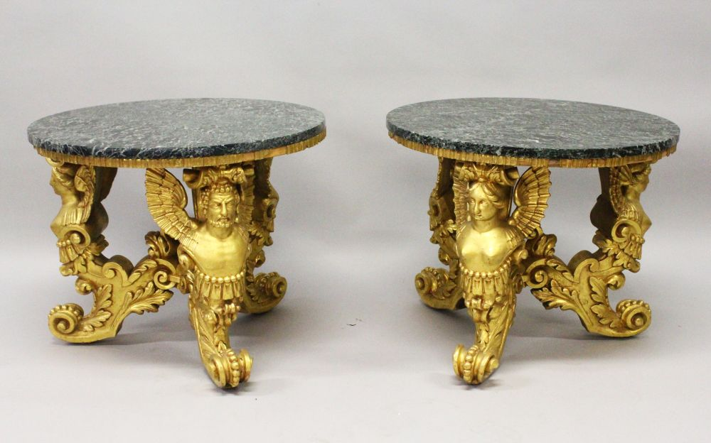 Lot 1017 - A GOOD PAIR OF 20TH CENTURY CARVED AND GILDED CIRCULAR LOW TABLES, with marble tops, the bases
