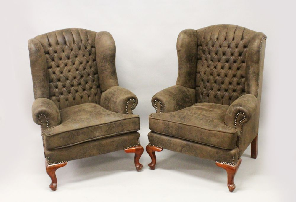Lot 1013 - A PAIR OF GEORGE III STYLE BUTTON UPHOLSTERED WING ARMCHAIRS, on cabriole legs.