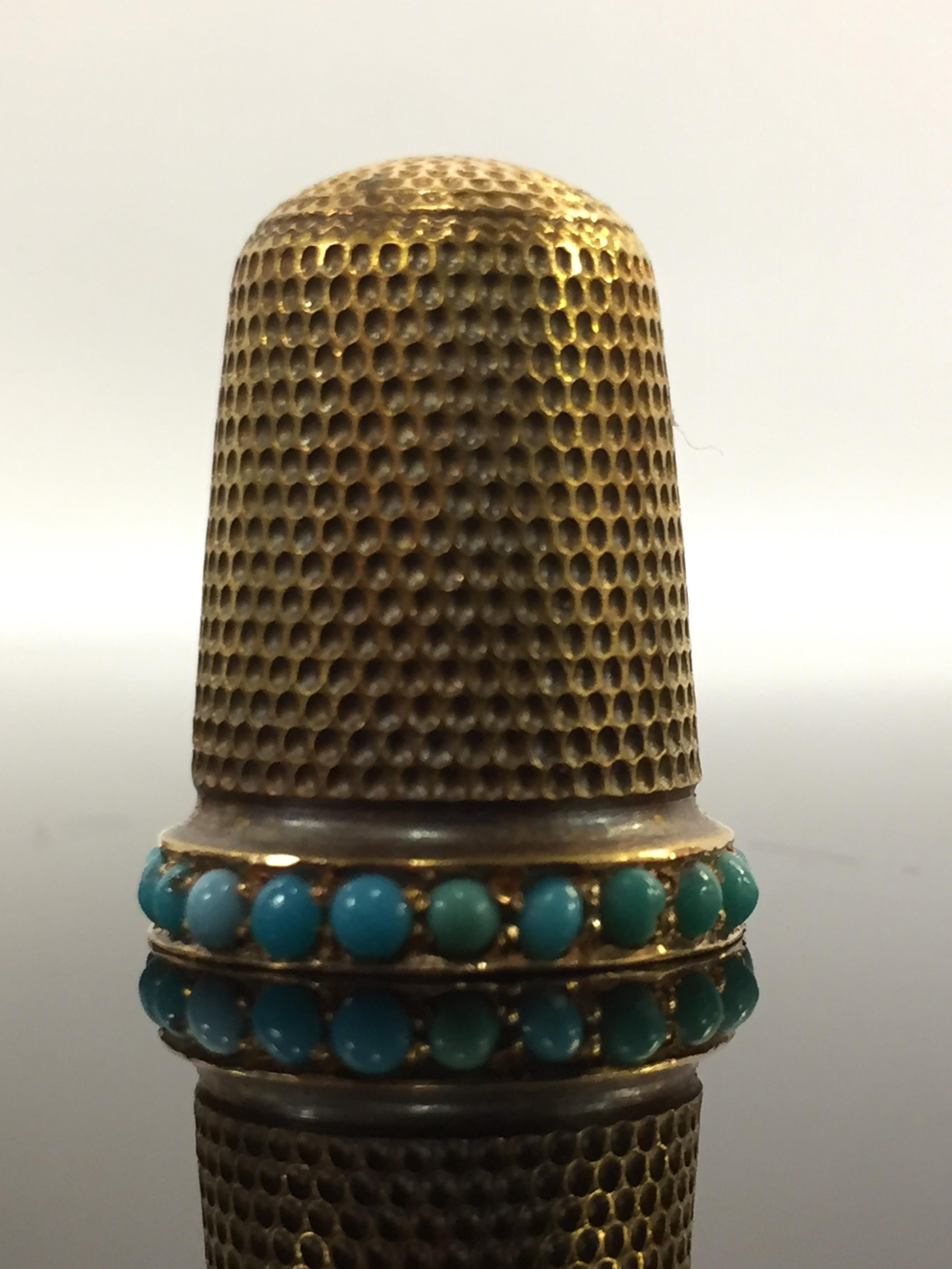 Lot 120 - A 15CT ROSE GOLD THIMBLE SET WITH A TURQUOISE RIM. PRESENTED IN AN ASPREY BOX.