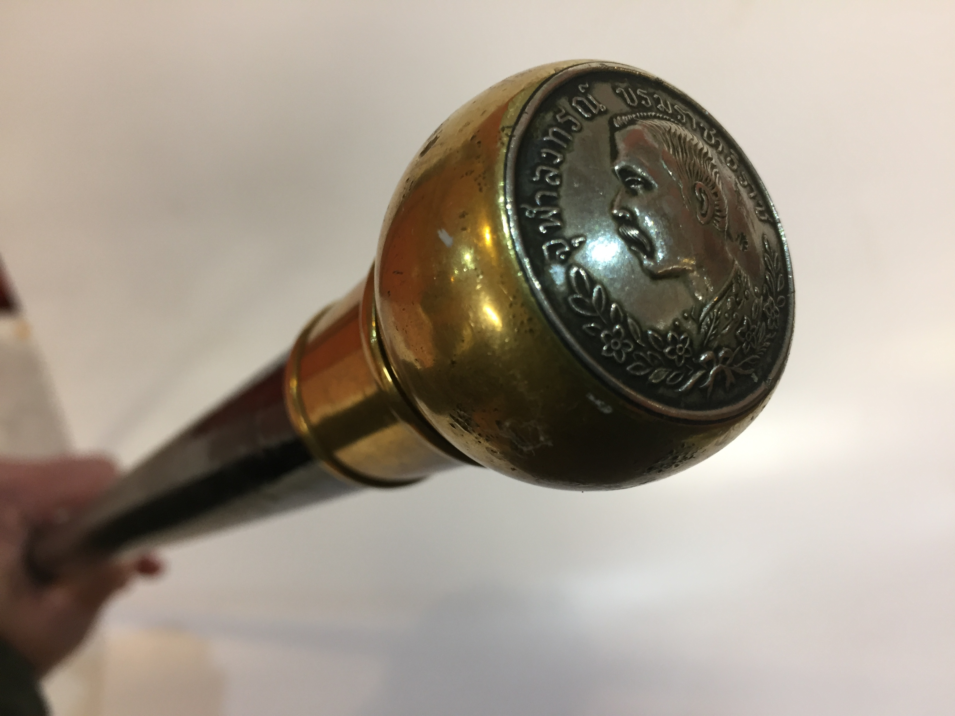 Lot 12 - WALKING STICK WITH BRASS KNOB MOUNTED WITH THAI KING COIN