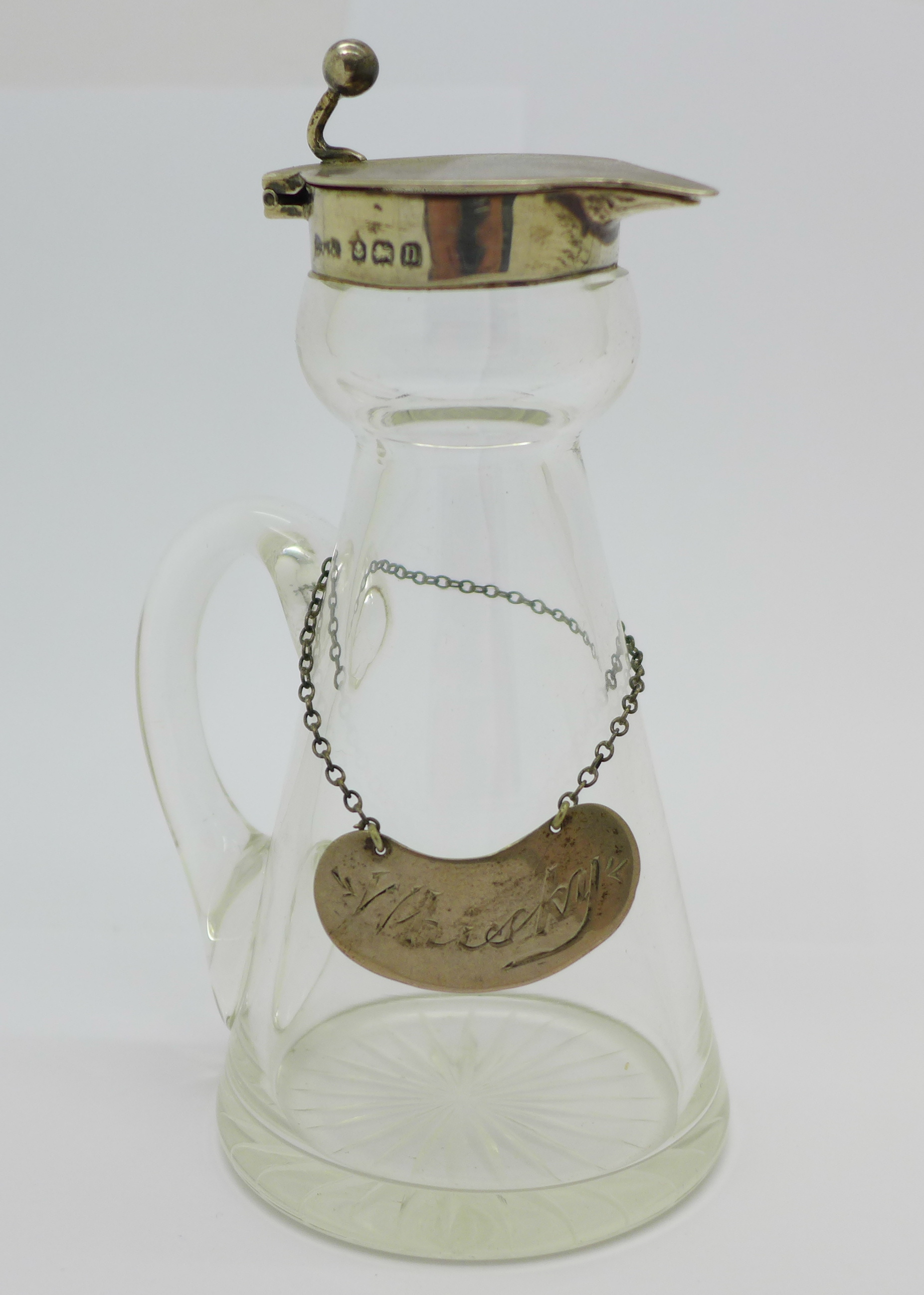 A silver mounted glass whisky noggin with a silver label