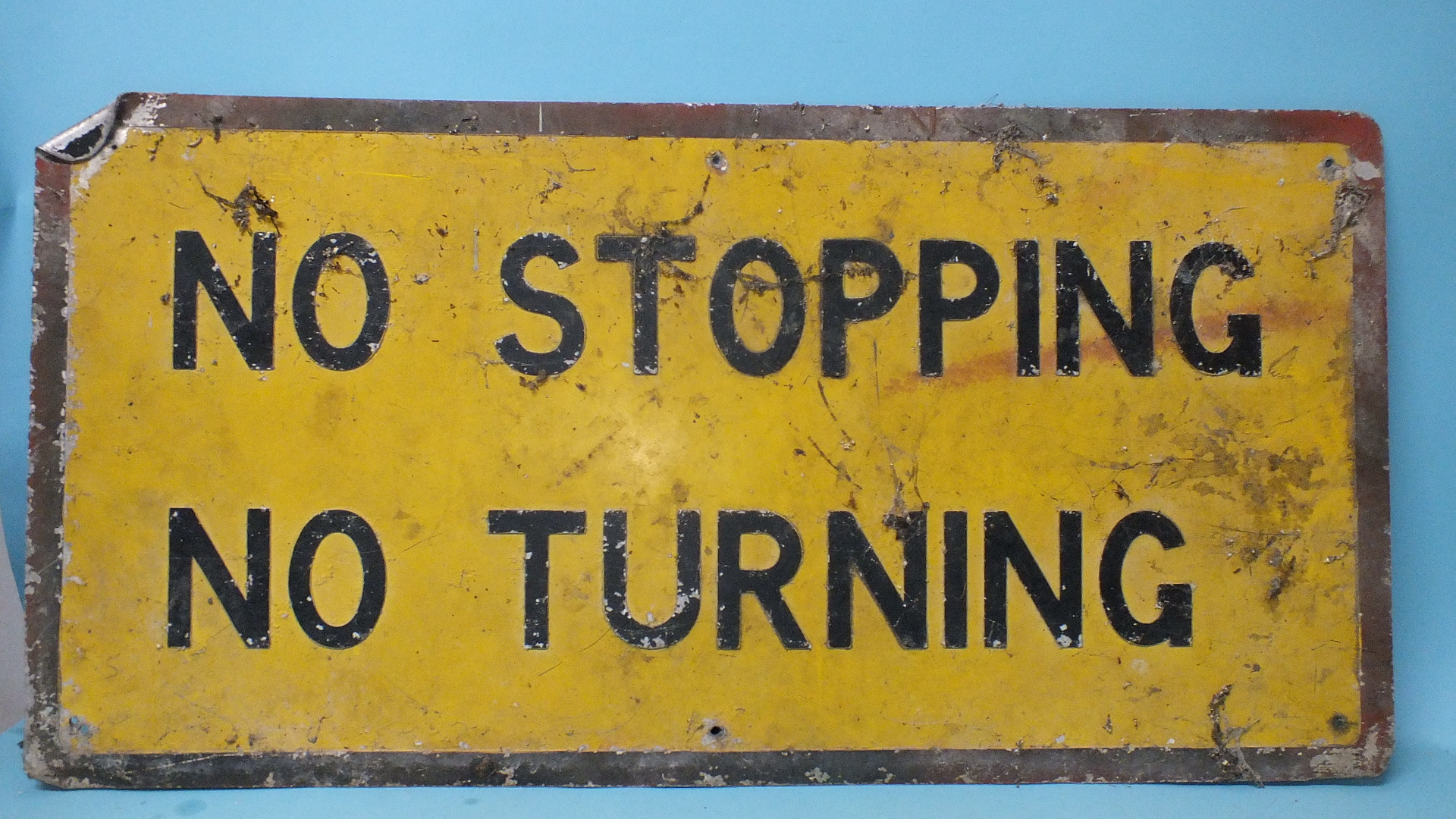 """Lot 363 - A yellow and black enamel road sign, """"No Stopping No Turning"""", 51 x 100.5cm, (a/f, one corner"""