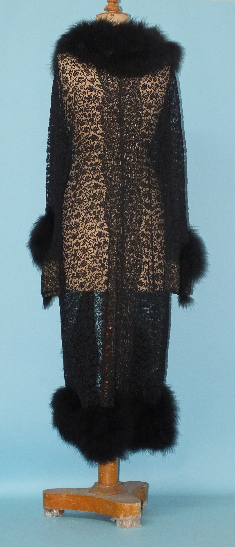 Lot 226 - A full-length evening coat of black machine-made lace, the collar, cuffs and hem trimmed with