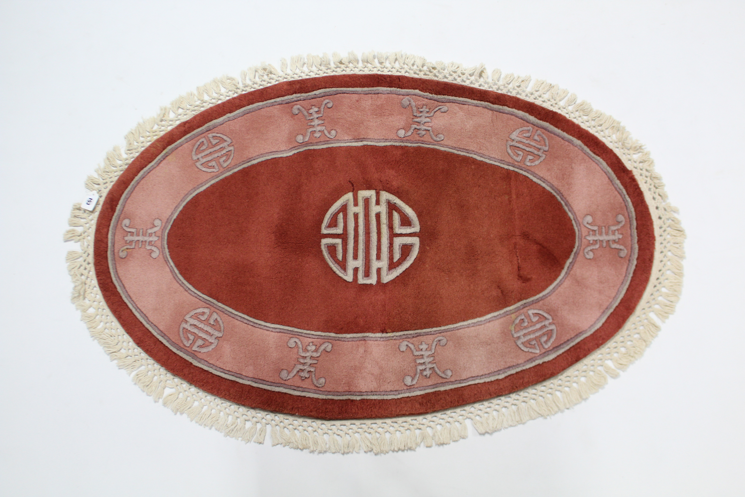 """Lot 153 - A pair of Chinese oval rugs of pink & coral ground, 50"""" x 31""""."""