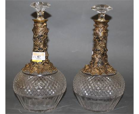 A pair of gilded white metal and cut glass bottle shaped decanters and stoppers, the mounts castors fruiting vines with diamo