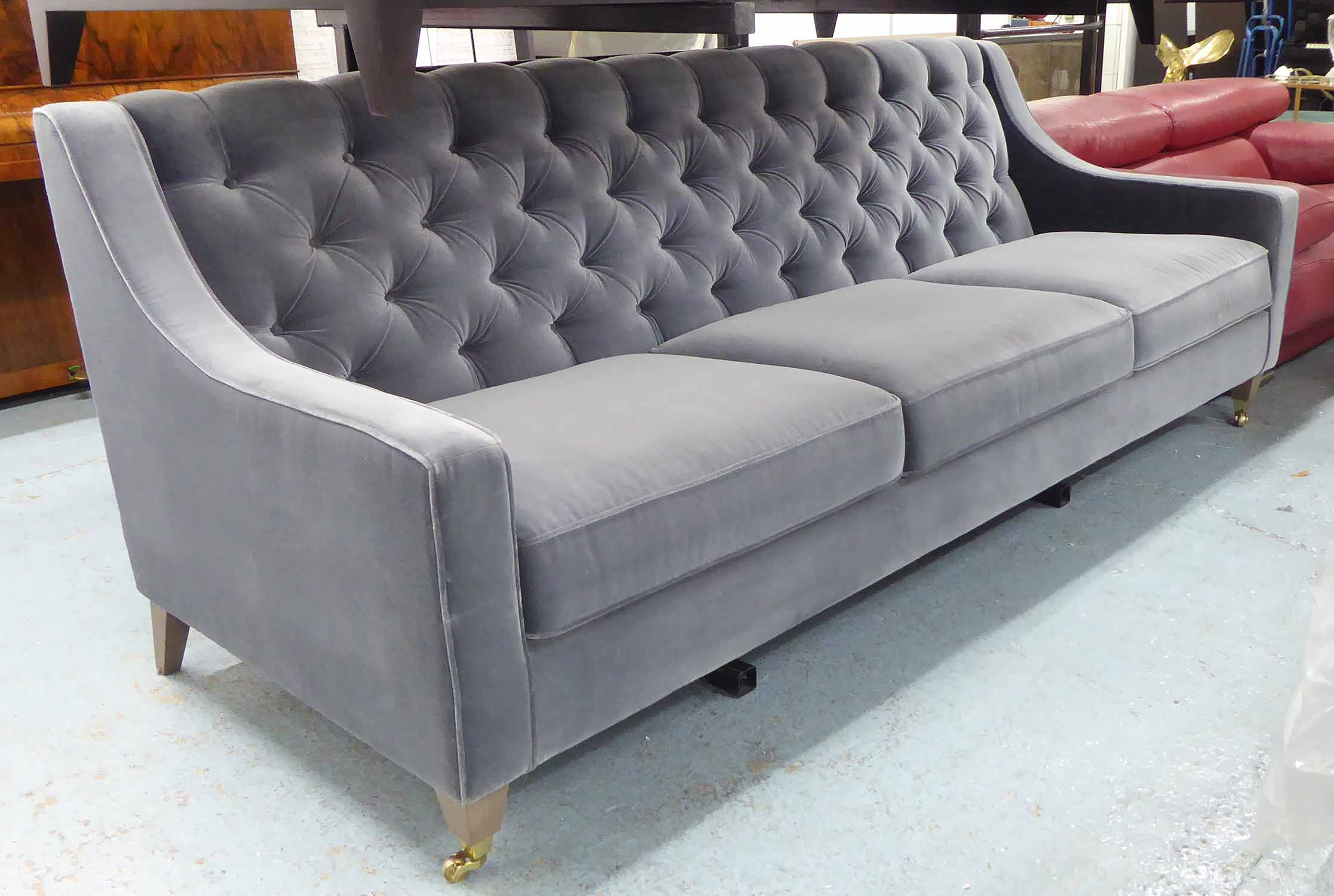 Lot 26 - SOFA, three seater, in grey button back velvet, on square castor support, 240cm L.
