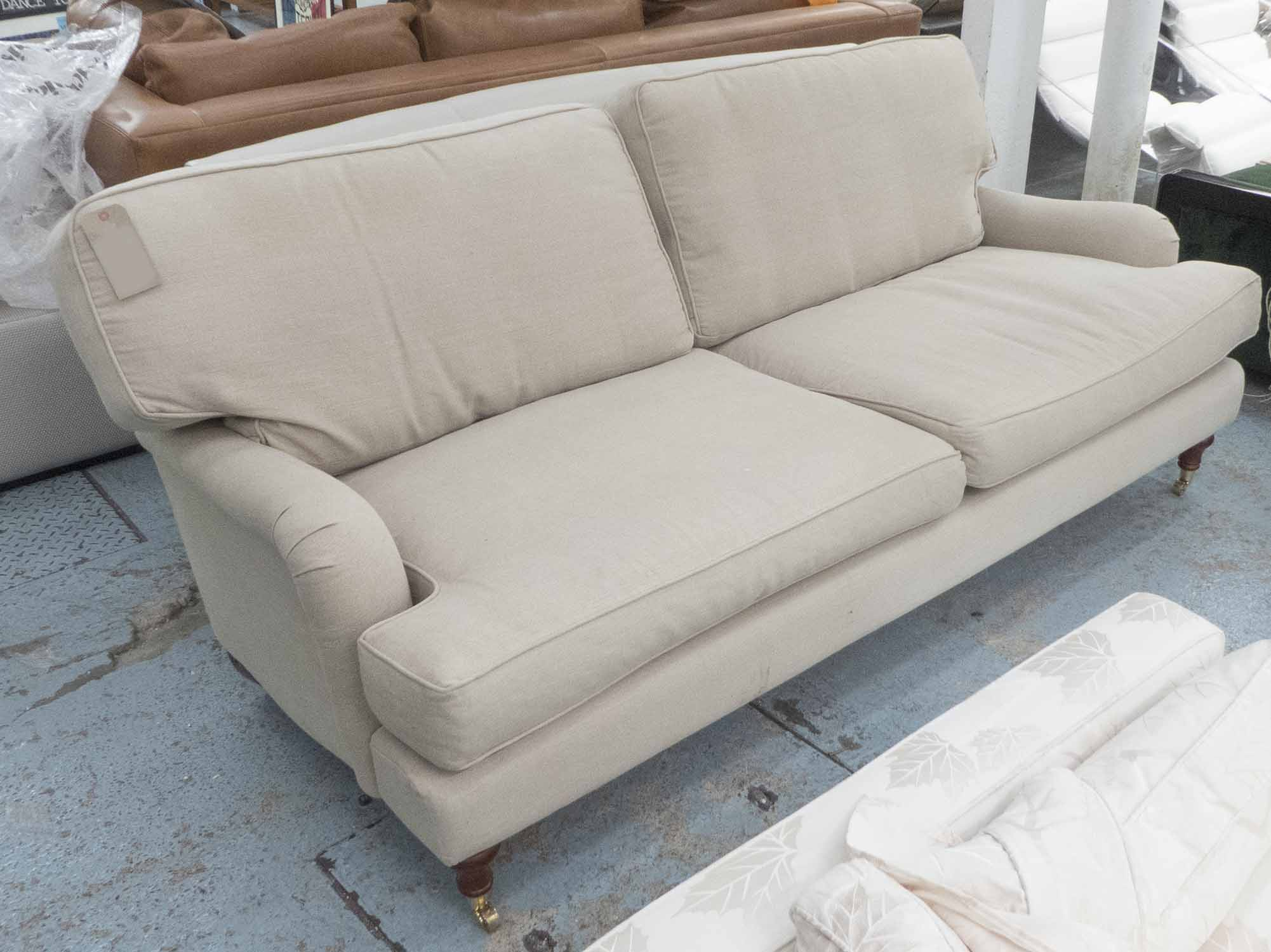 Lot 29 - SOFA, two seater, Howard style, in beige fabric on turned castor supports, 212cm L.