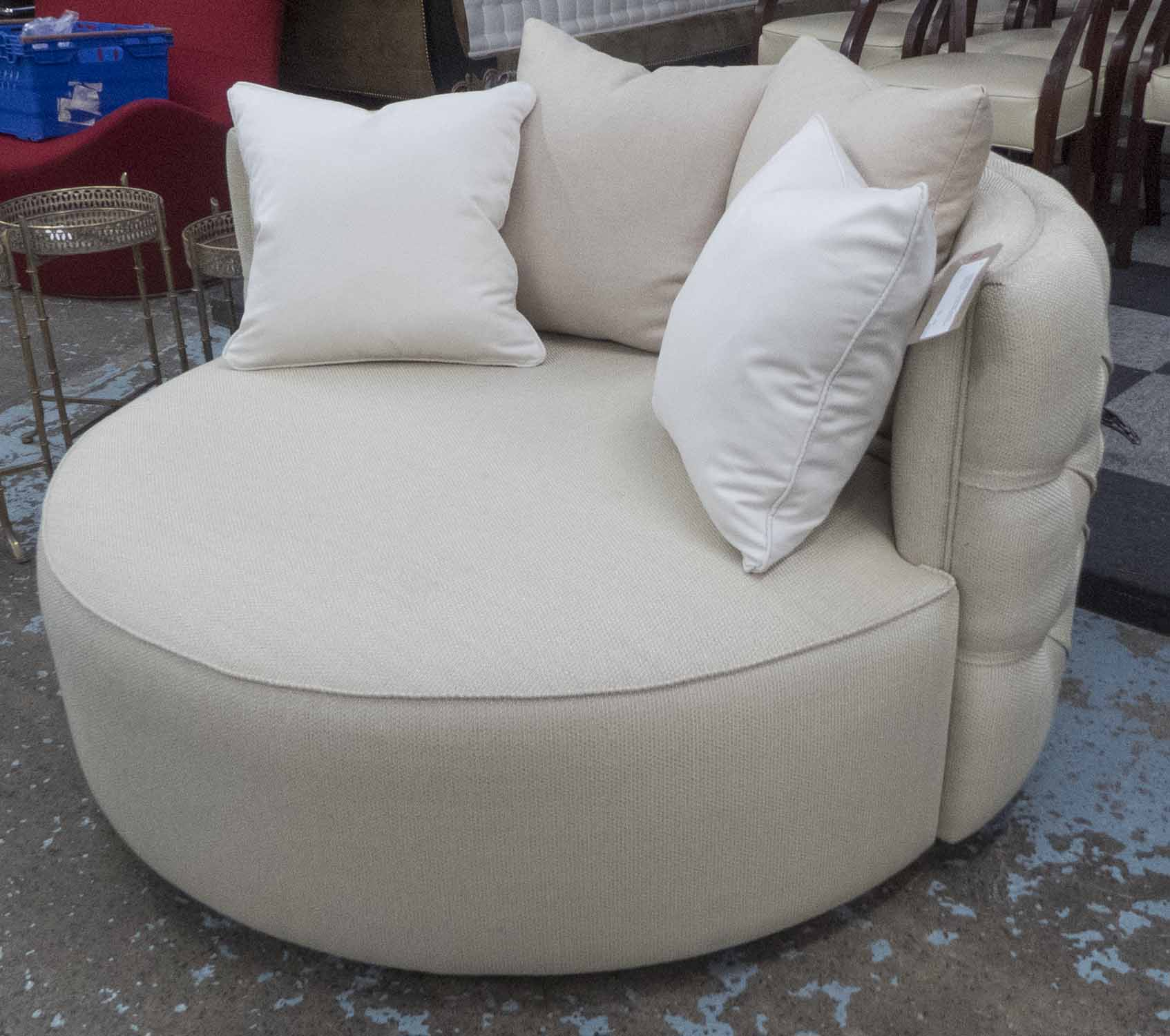 Lot 34 - ROUND SOFA, in a beige fabric, external buttoned back, on an ebonised swivel support, 135cm diam.