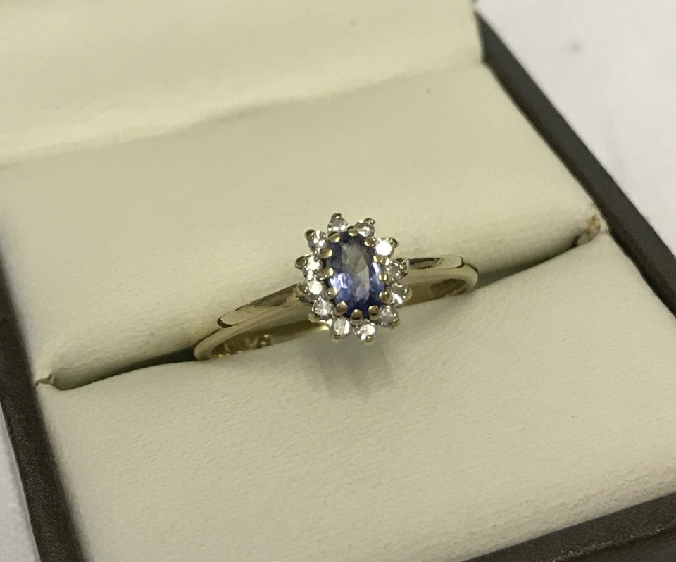Lot 36 - Pretty hallmarked 9ct gold ring set with oval sapphire surrounded by small diamonds.