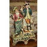 """A late 19th century Continental pottery figure group, hunter with his lady, in period costume, 21"""""""