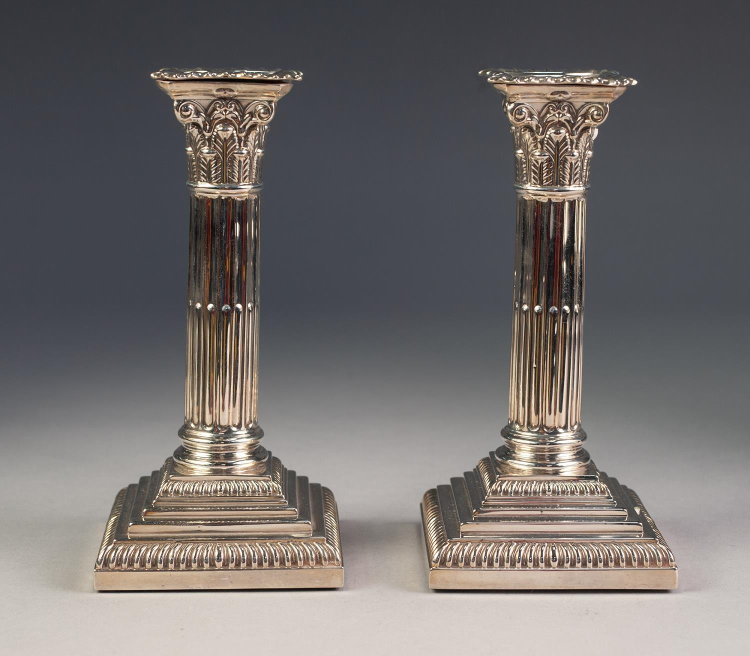Lot 258 - A PAIR OF EDWARDIAN WEIGHTED SILVER CORINTHIAN COLUMN CANDLESTICKS WITH REMOVABLE GADROONED NOZZLES