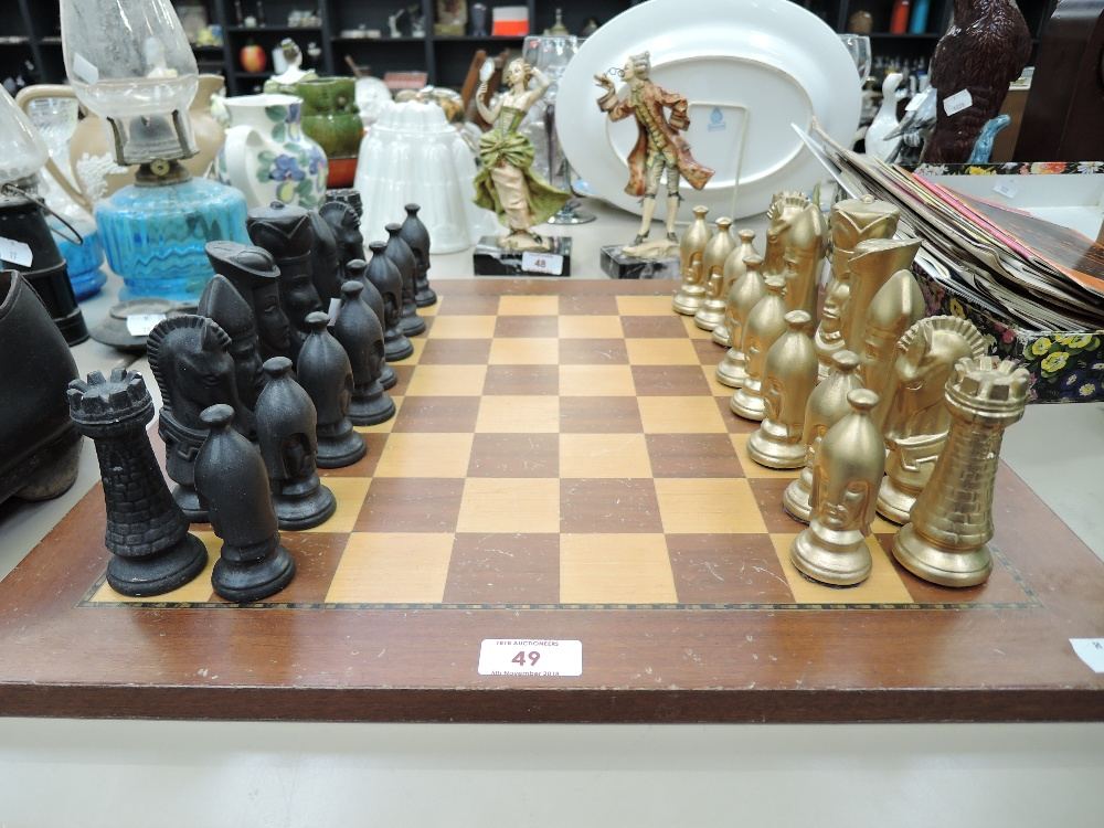 Lot 49 - A vintage chess set with wood board and black and gold pieces