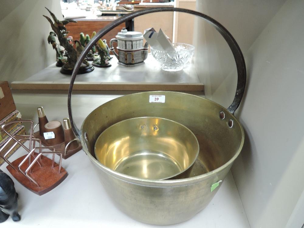 Lot 39 - A vintage brass jam pan and similar