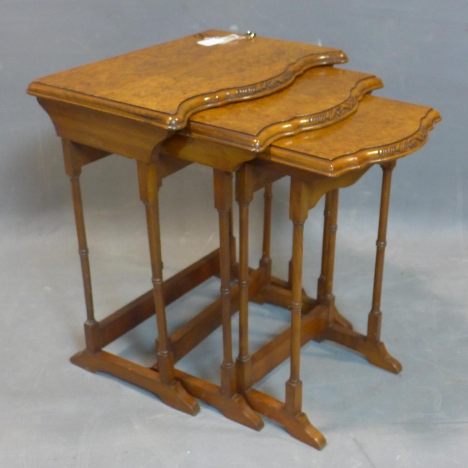 A walnut nest of three tables, with quarter veneered tops with serpentine fronts, raised on