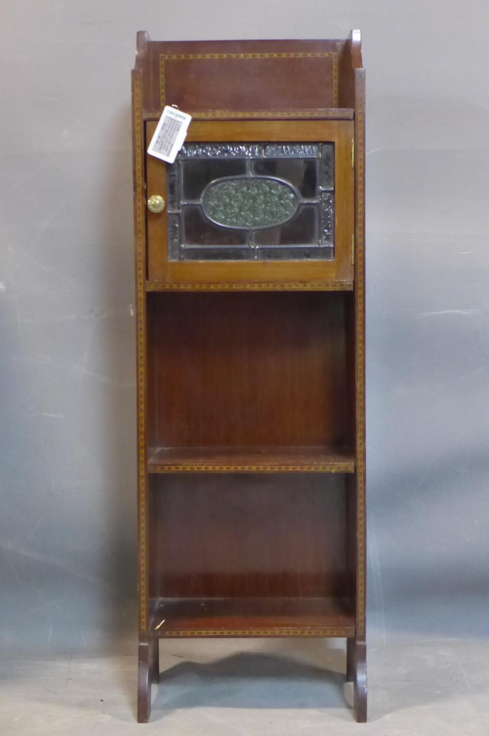 A small Arts and Crafts mahogany and inlaid narrow side cabinet, with single leaded glass door above