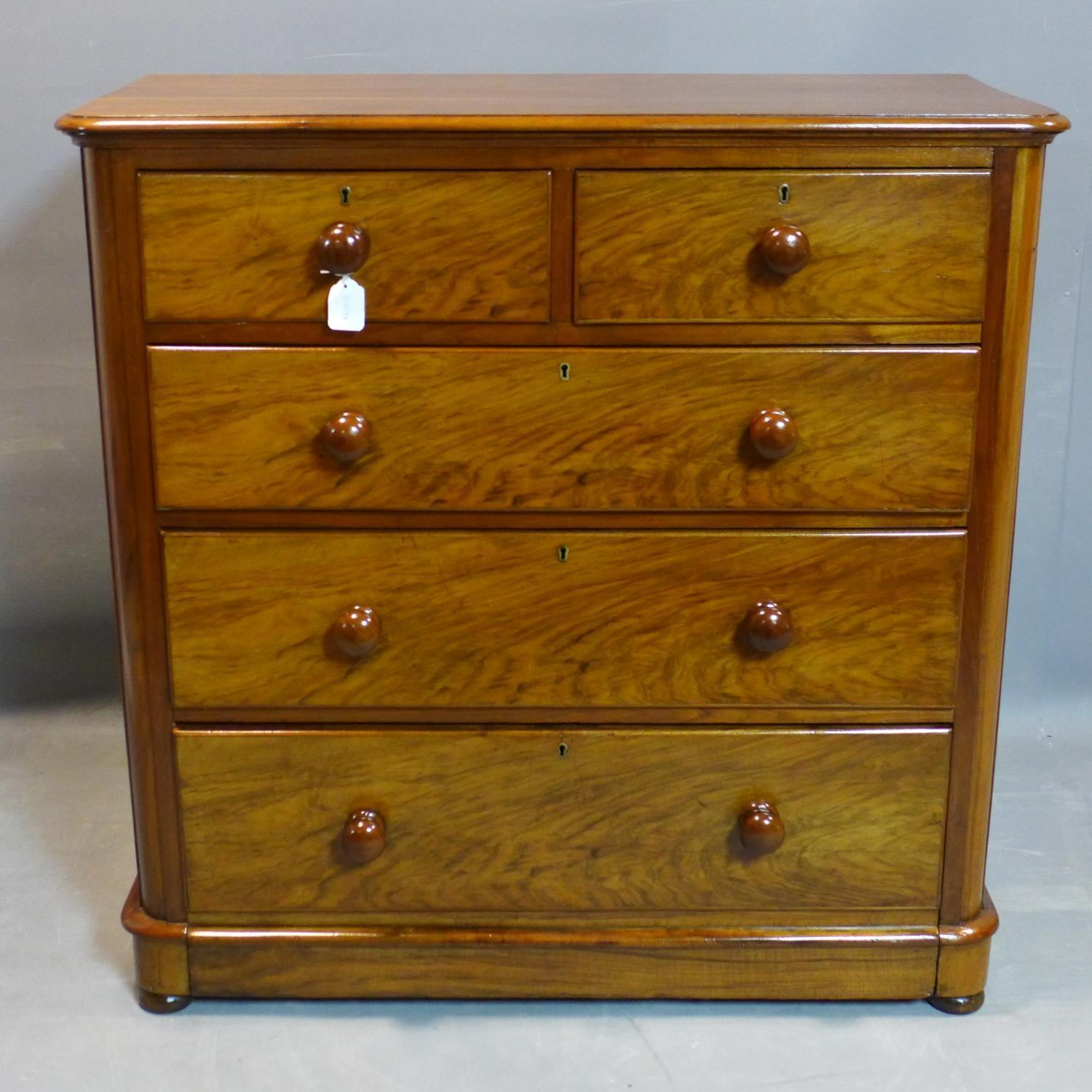 Lot 123 - A Victorian walnut chest of two short over three long drawers, on pedestal base and bun feet, H.
