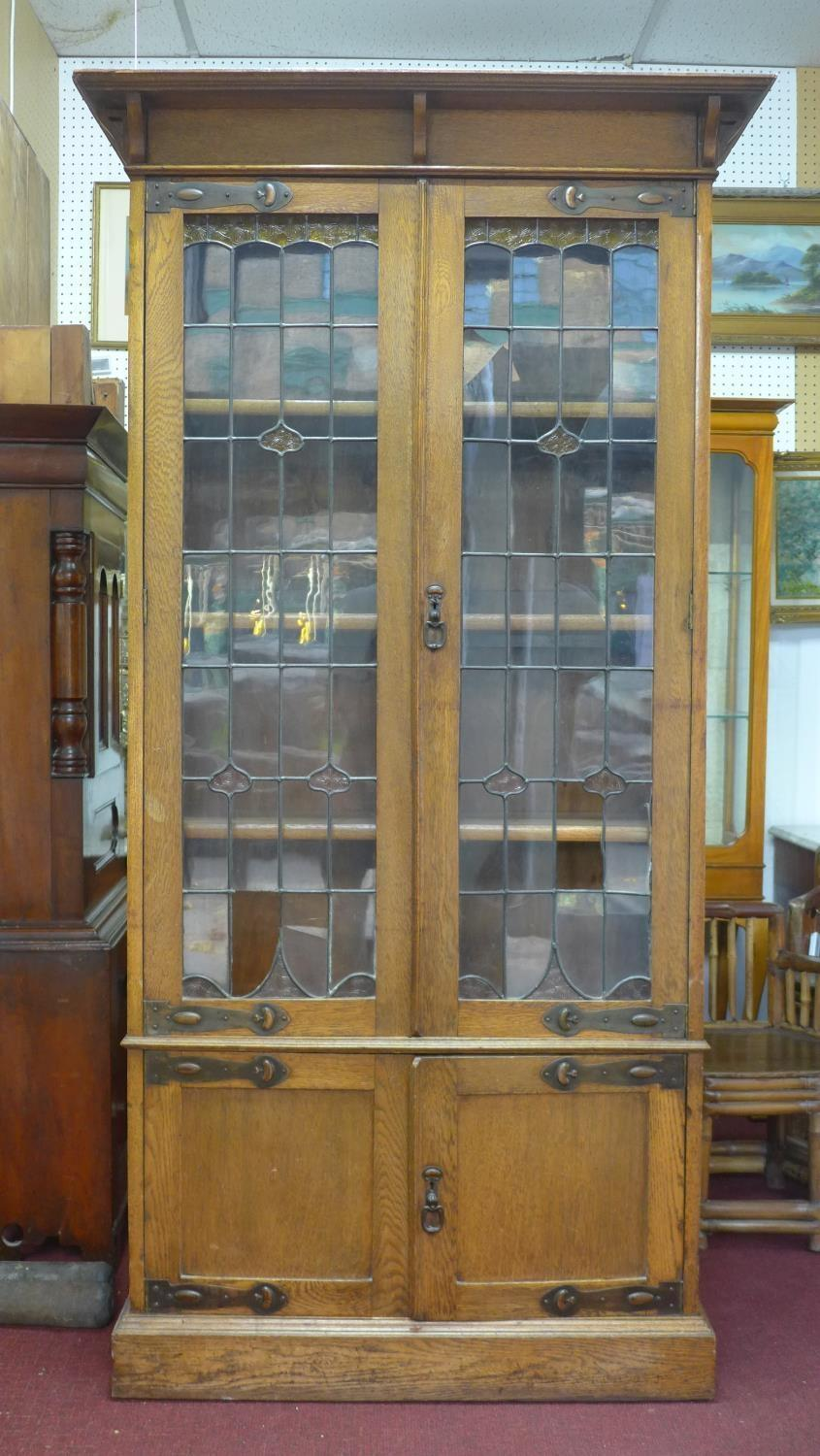 Lot 174 - A 19th century Arts & Crafts oak cabinet with moulded cornice above two leaded glass doors with