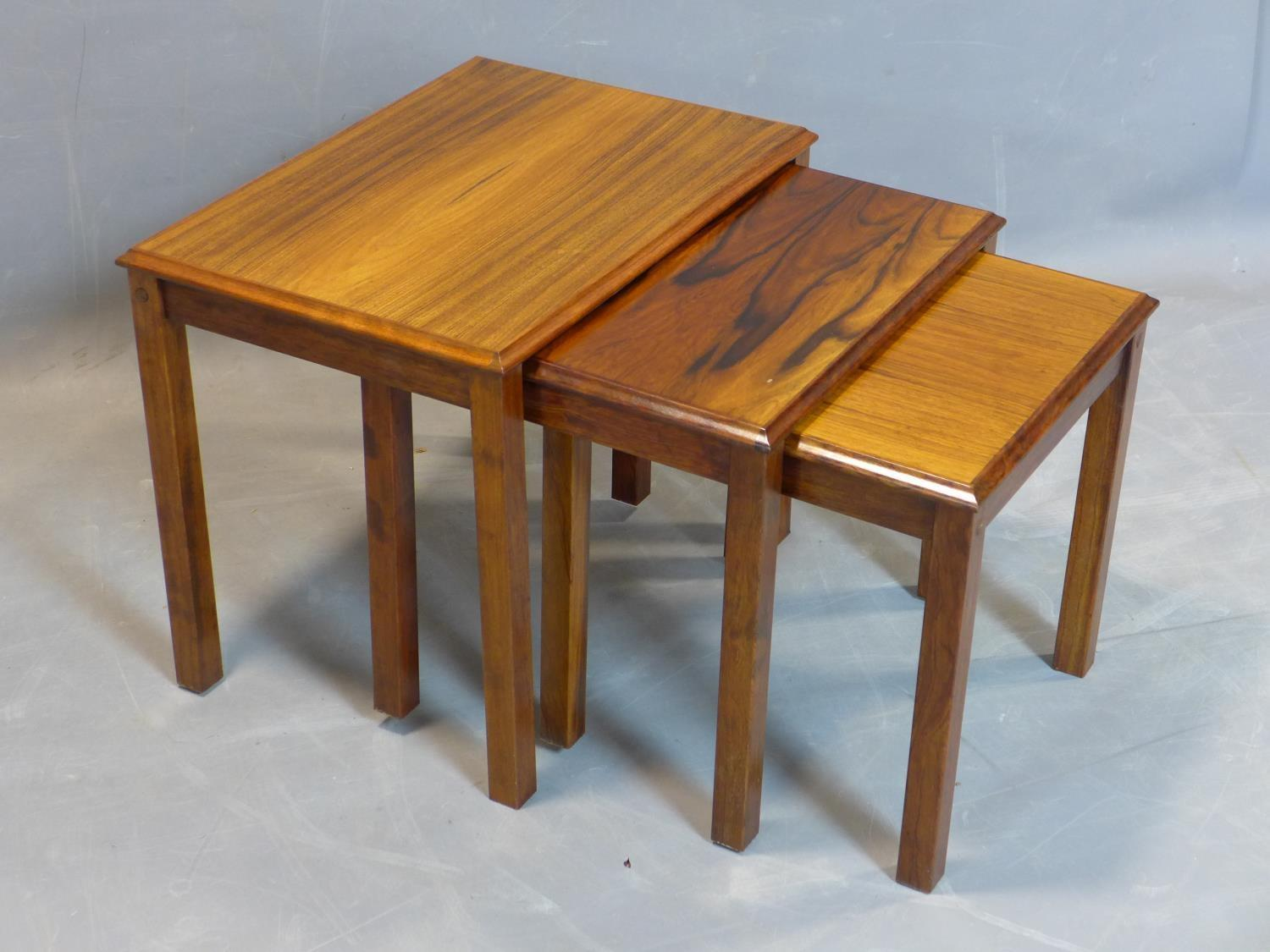 A nest of three Danish exotic hardwood tables, marked 'Made in Denmark' to bases, H.46 W.54 D.39cm