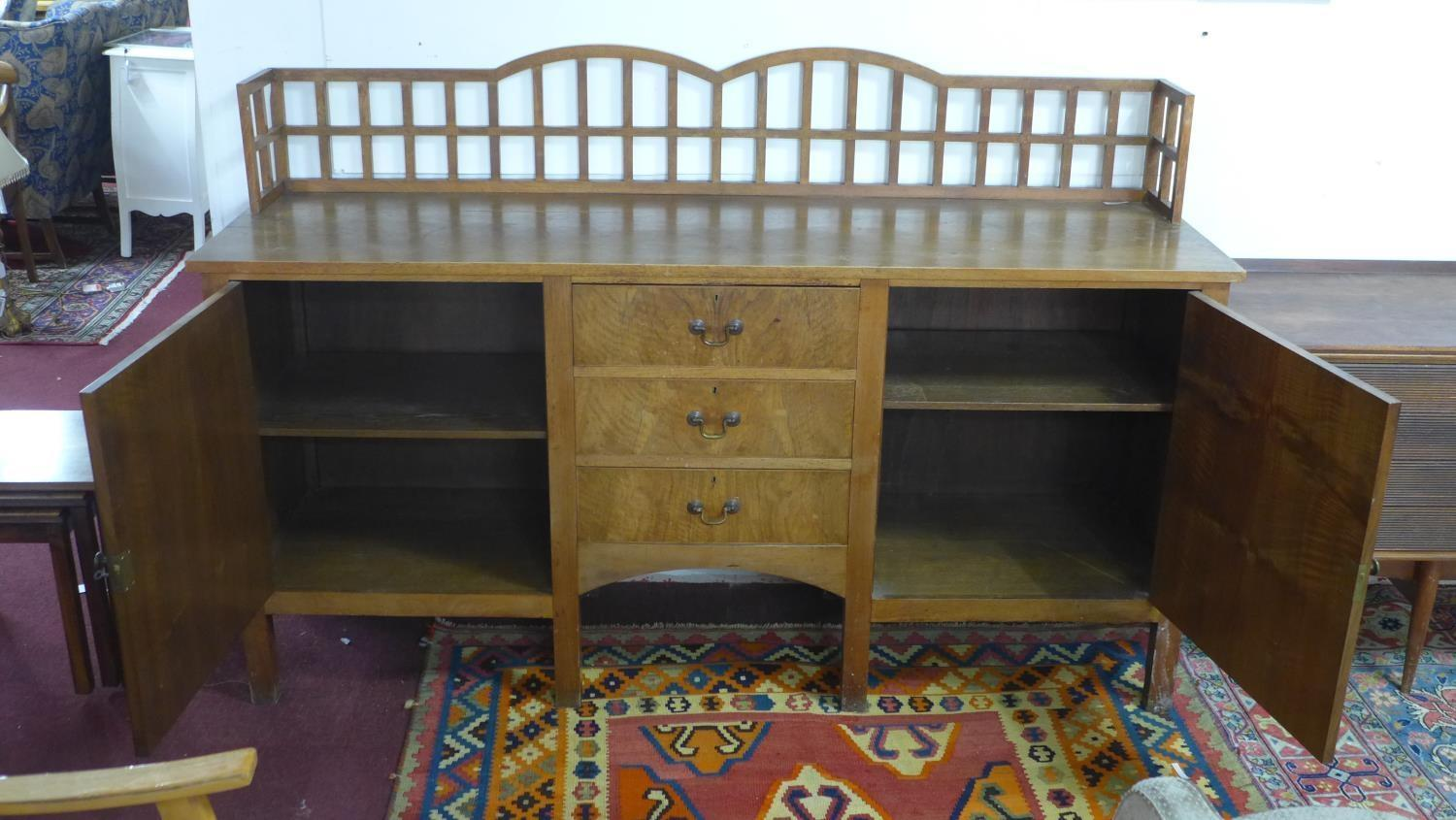 Lot 177 - A mid 20th century walnut sideboard, having gallery back above three central drawers flanked by