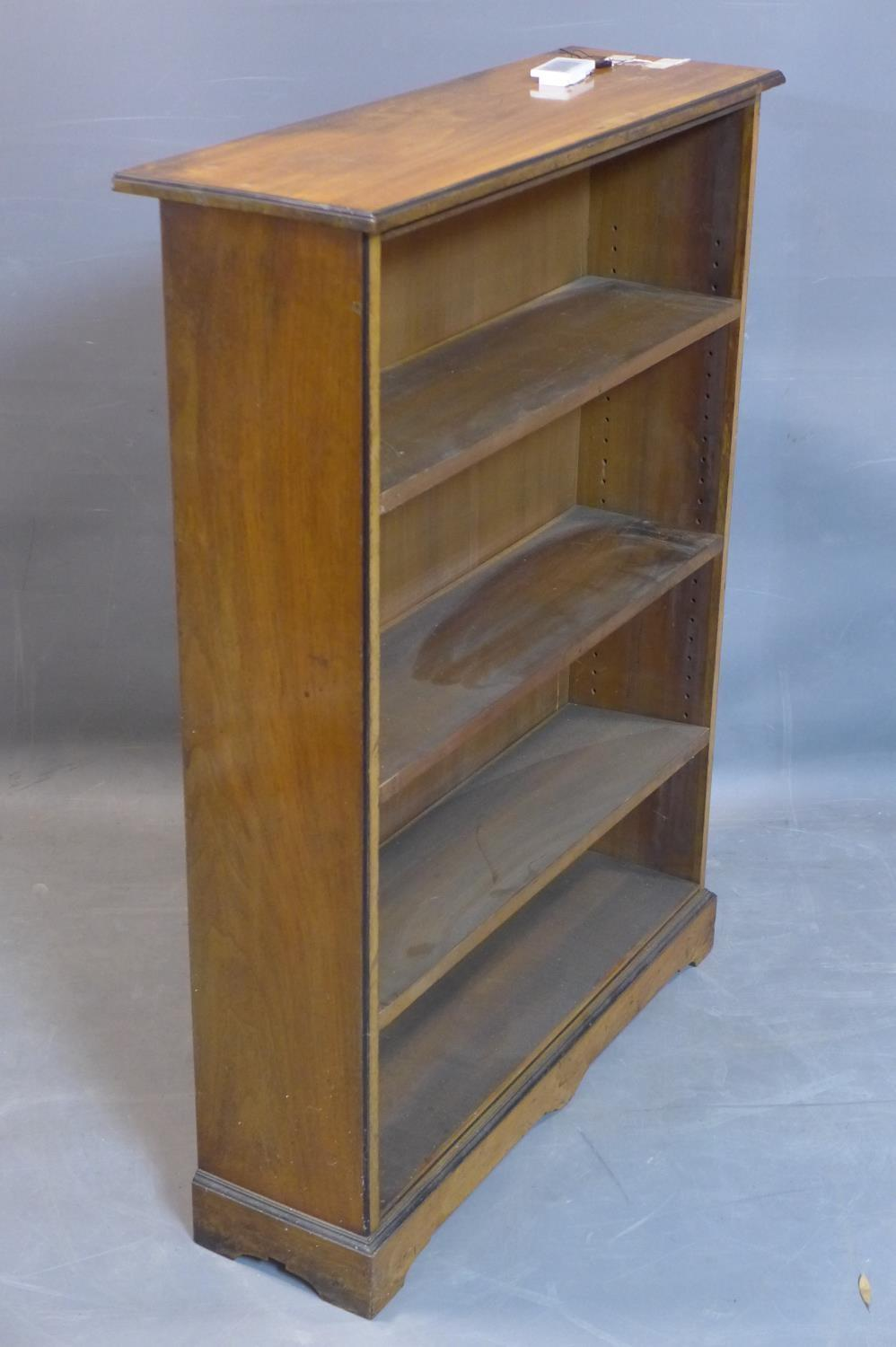 Lot 248 - An Edwardian mahogany open bookcase, with ebonised edges, raised on pedestal base and bracket feet