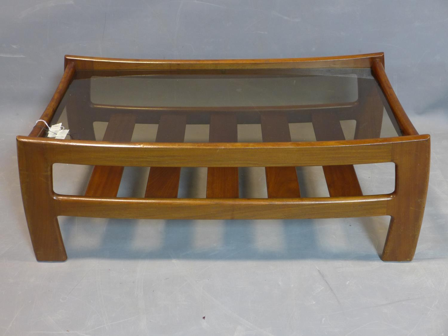 A mid 20th century teak coffee table, with glass top above undertier rack, H.40 W.105 D.53cm