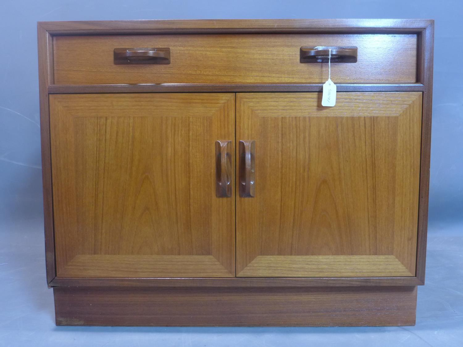 A G-plan teak cabinet, with one long drawer above two cupboard doors, on pedestal base, label to