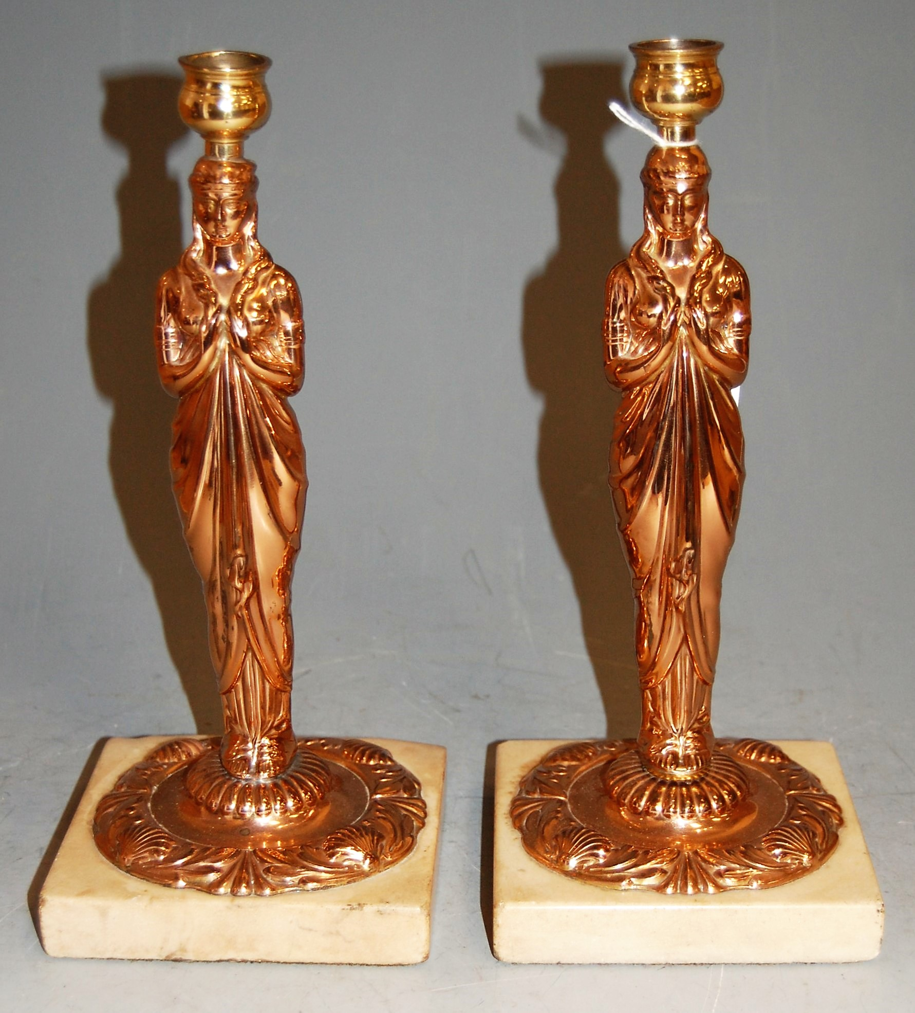 Lot 41 - A pair of copper figural candlesticks, each on a marble plinth, h.26cm