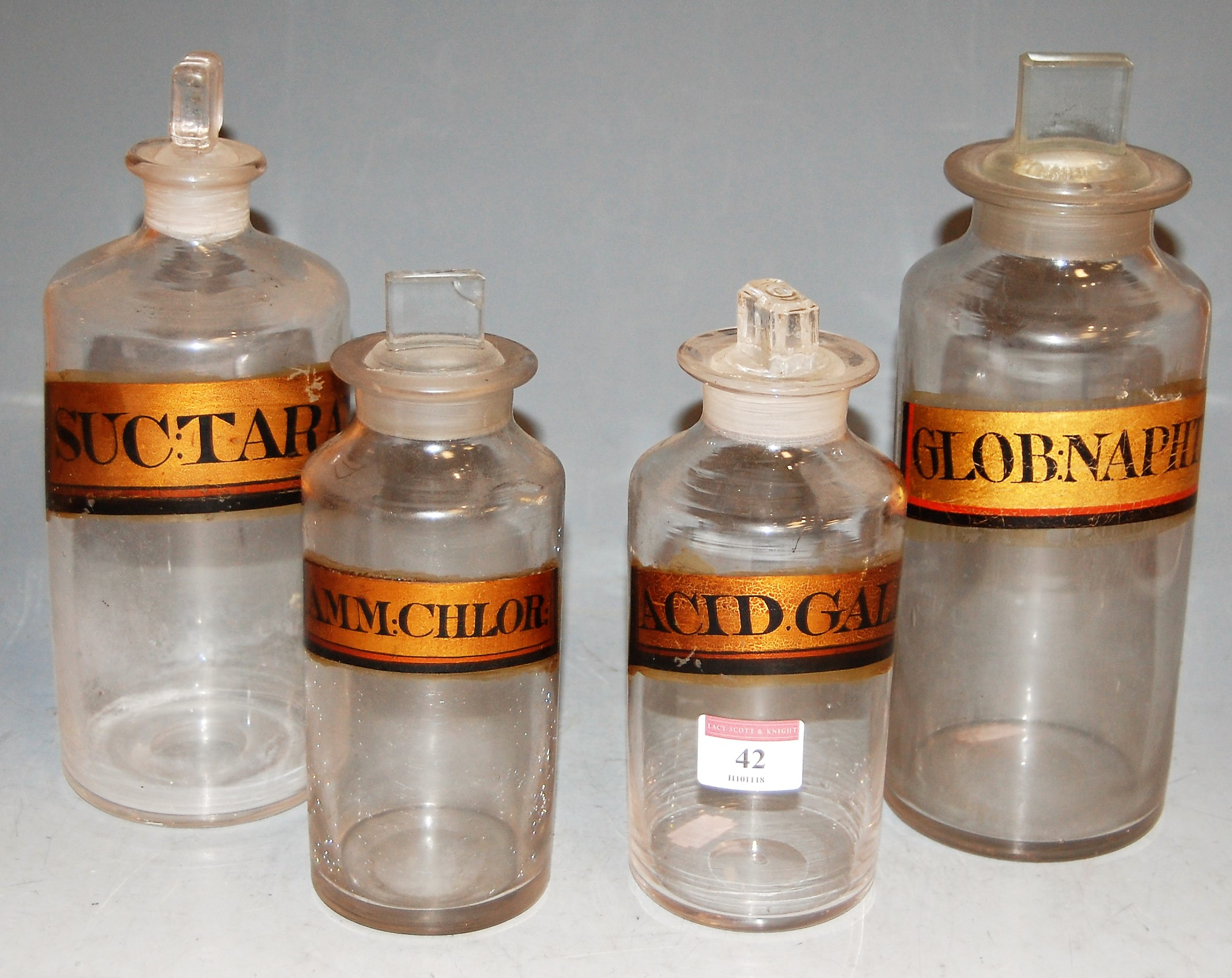 Lot 42 - Four early 20th century apothecary jars and stoppers, each with annotation, largest h.25cm