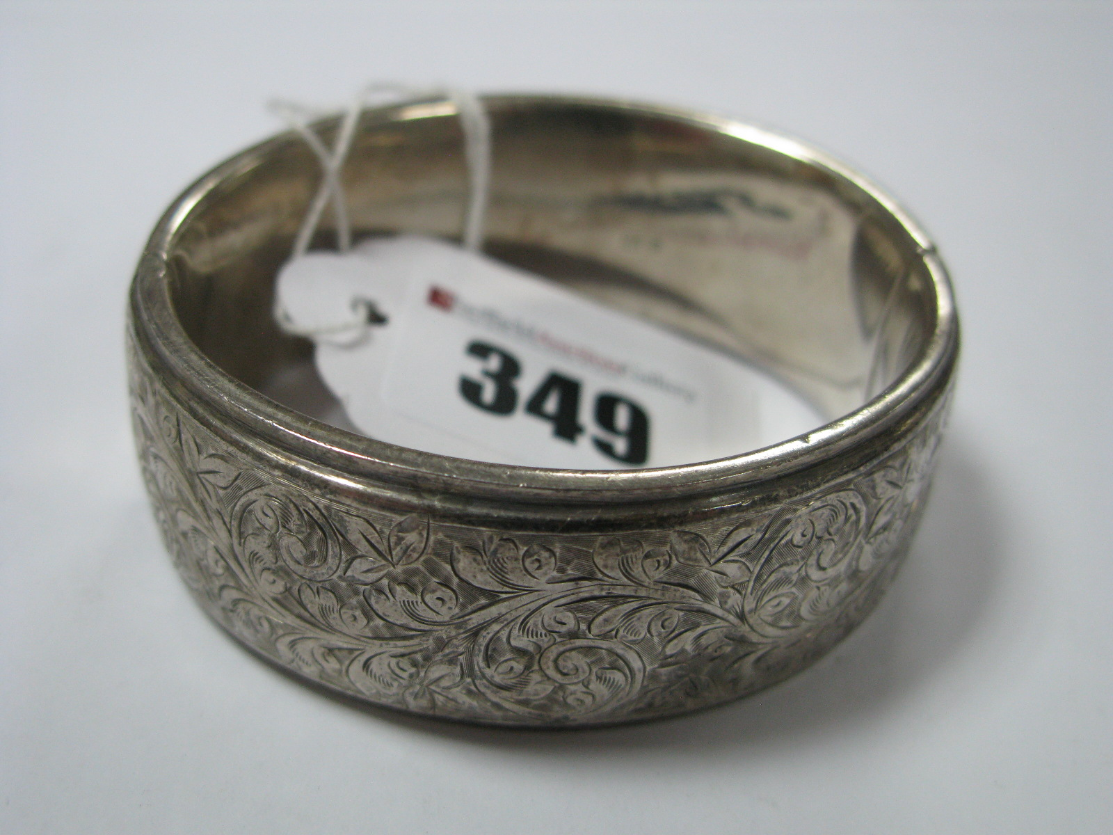 Lot 349 - A Wide Hallmarked Silver Bangle, with part foliate design.
