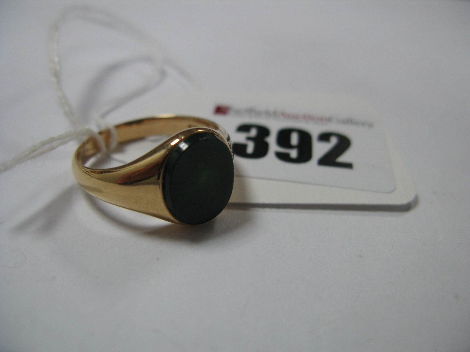 "Lot 392 - An Oval Hardstone Inset Panel Signet Ring, between plain setting and shoulders, stamped ""18""."