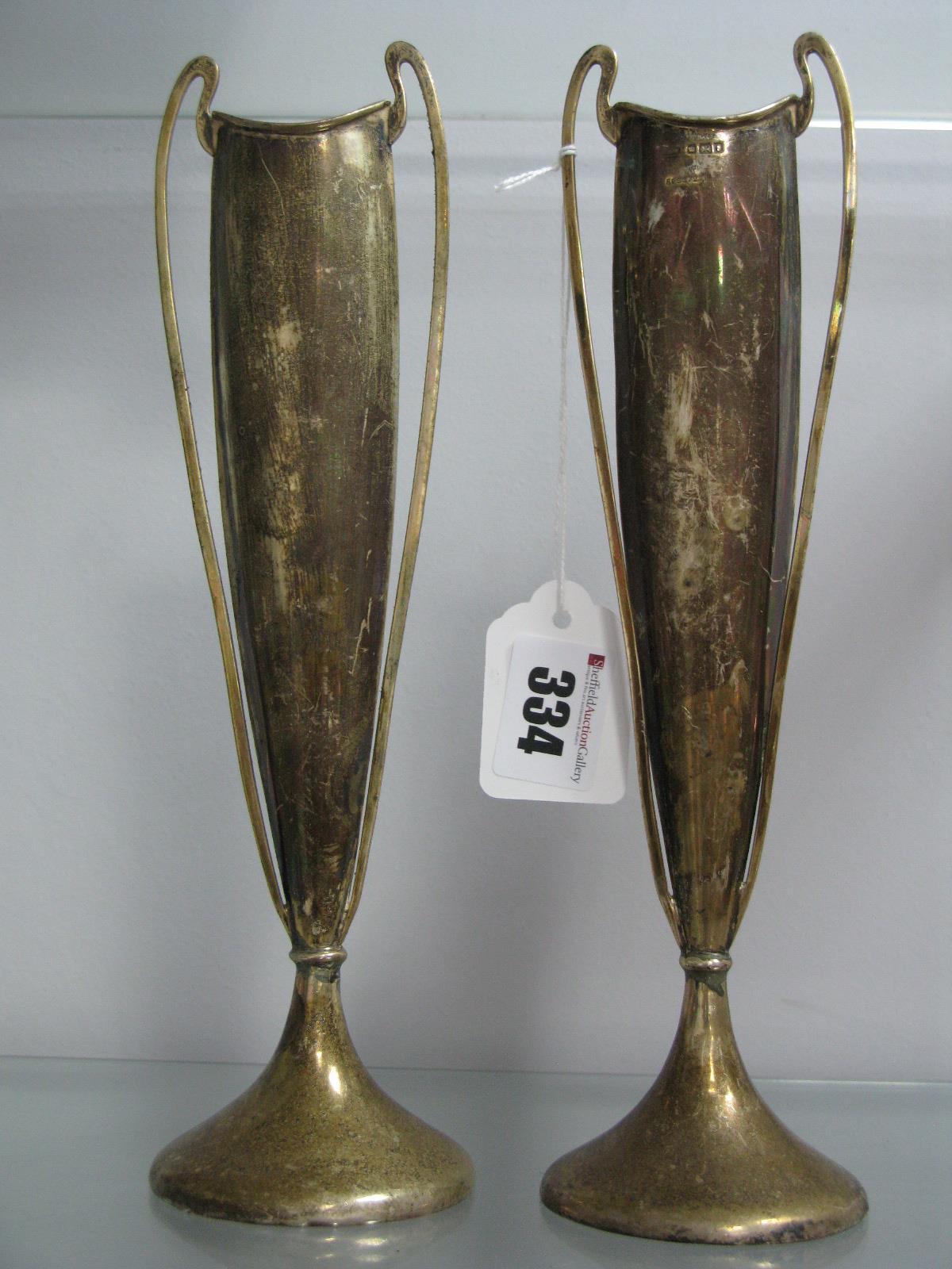Lot 334 - A Pair of Hallmarked Silver Vases,each of tall slender tapering form, with high loop handles, on