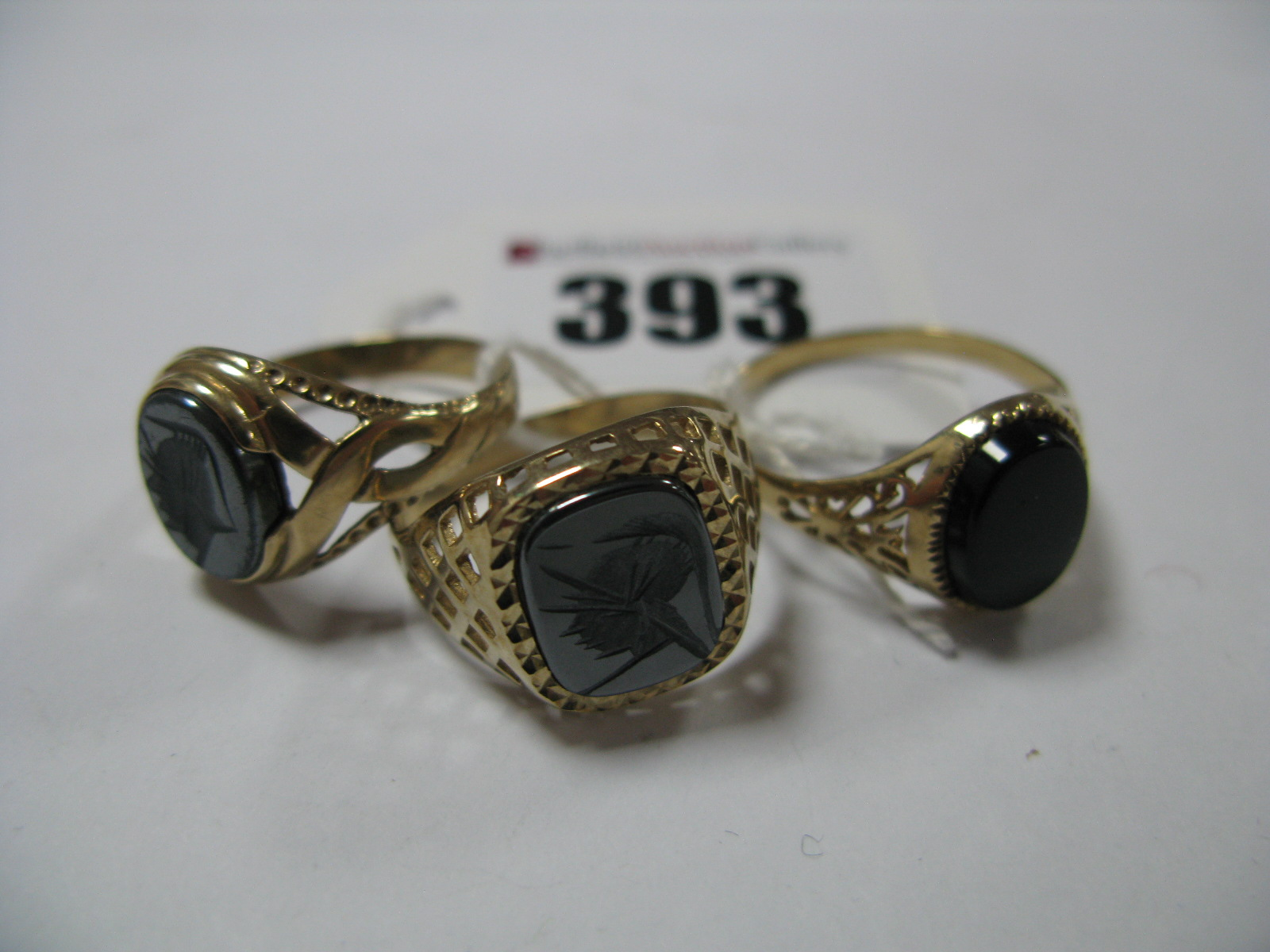 Lot 393 - Three 9ct Gold Gent's Signet Style Rings, with hardstone inset panels, between openwork textured