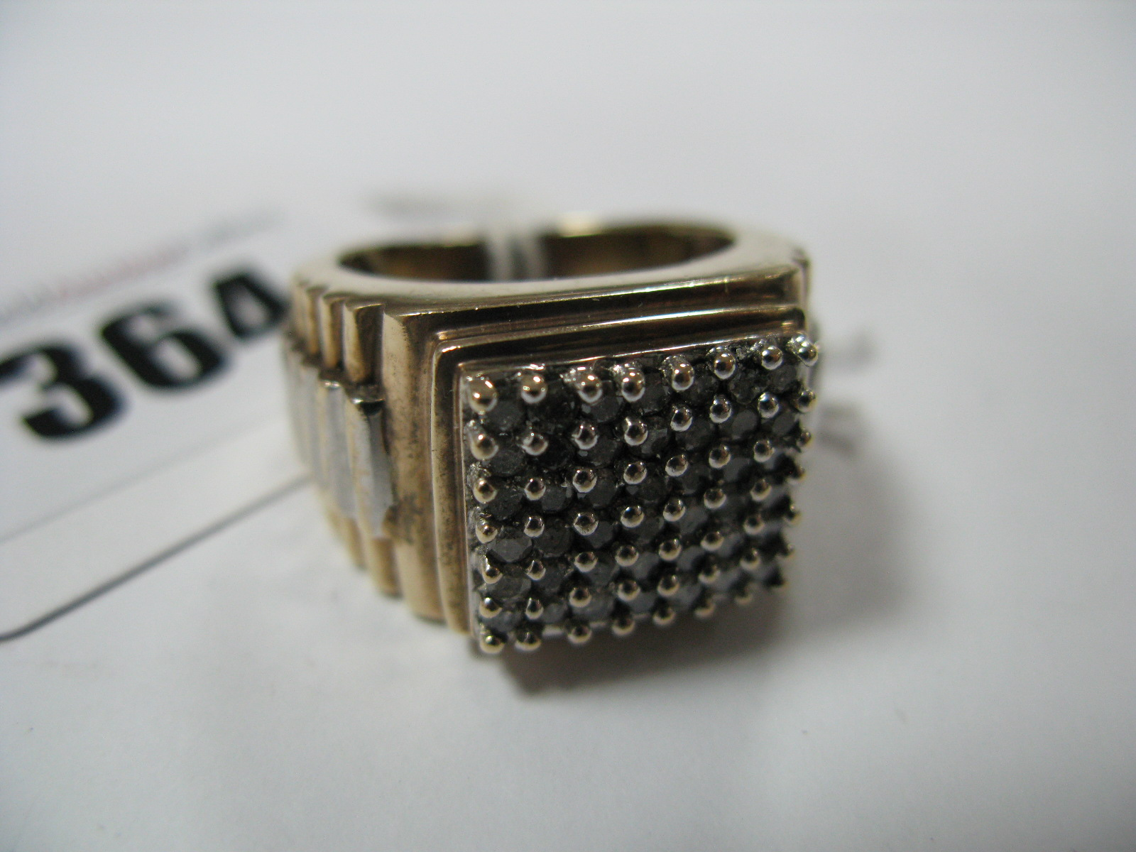 Lot 364 - A Large Gent's Dress Ring, square claw set to the centre, between textured watch bracelet style
