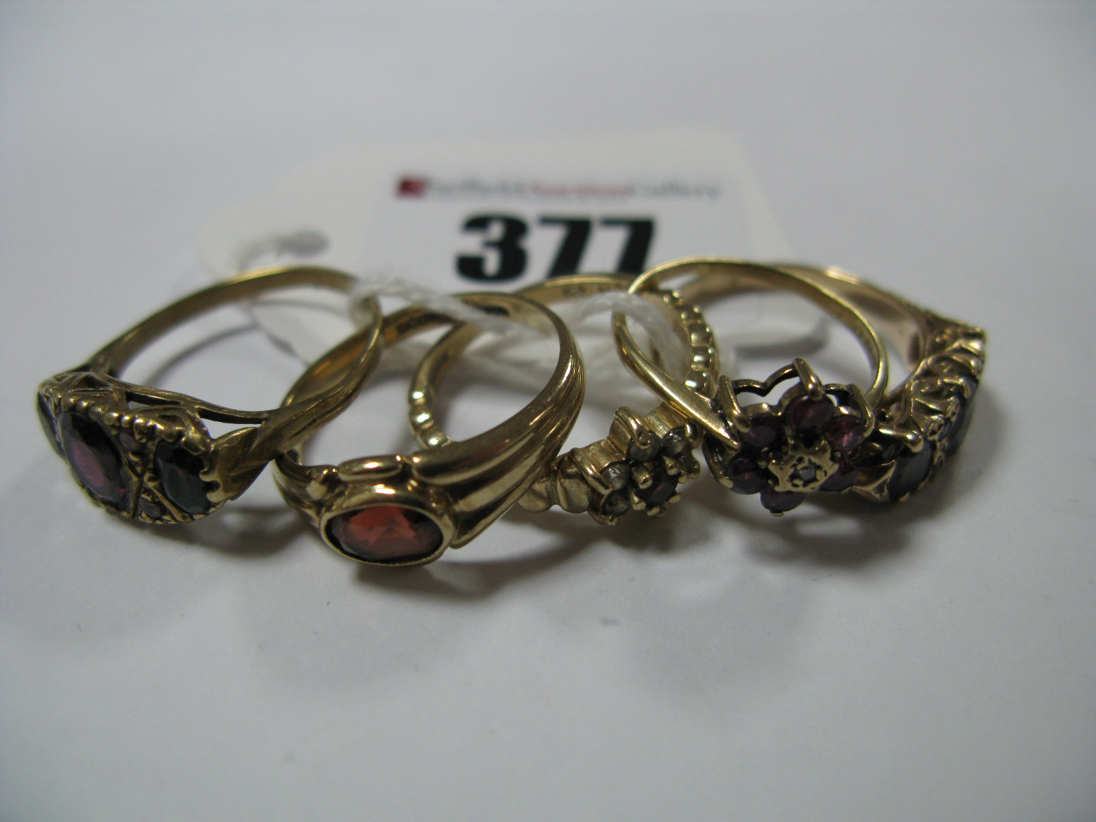 Lot 377 - A 9ct Gold Victorian Style Dress Ring, oval graduated set, between openwork setting and textured