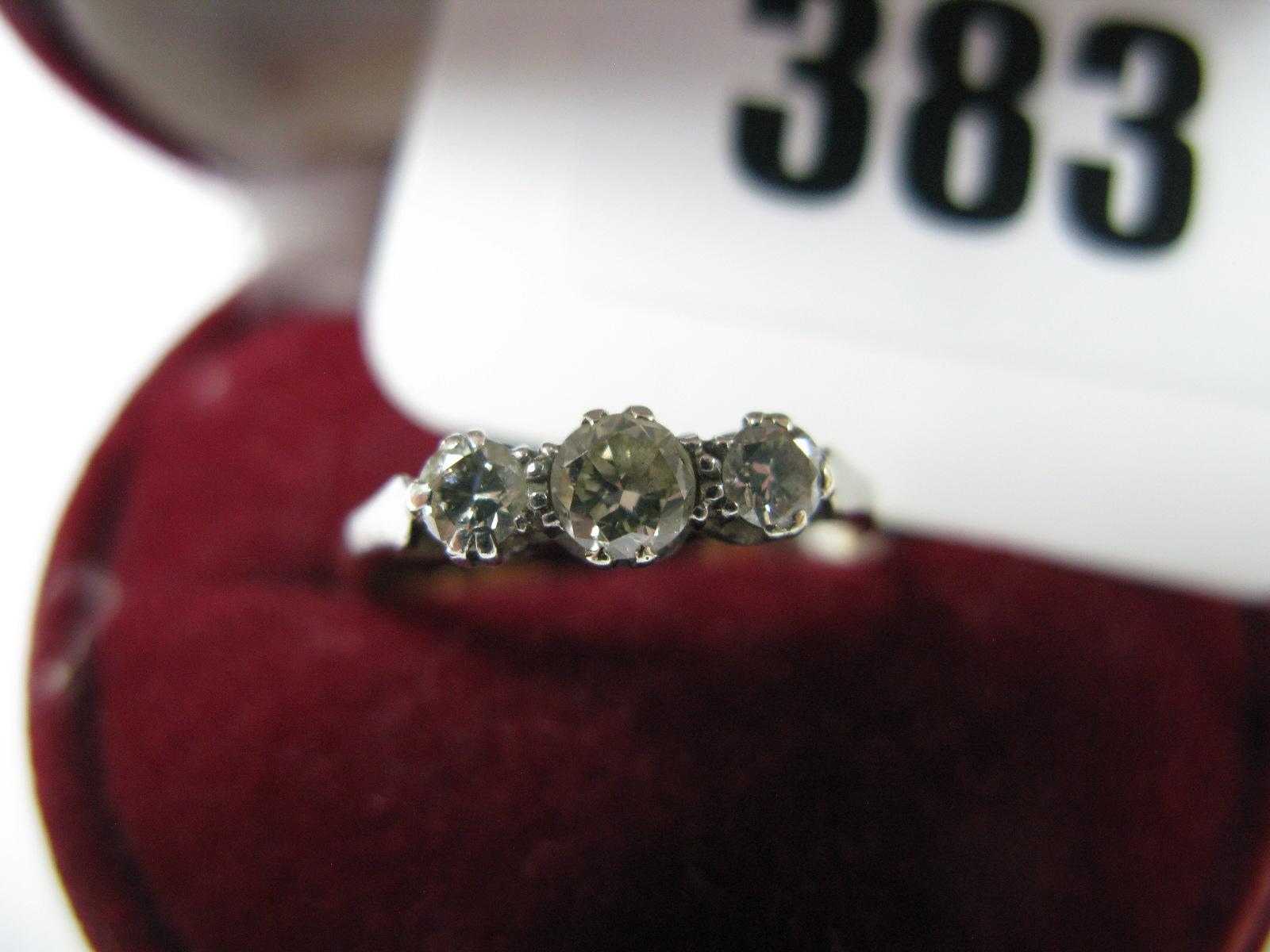 Lot 383 - A Three Stone Diamond Ring, the graduated brilliant cut stones claw set, between tapered