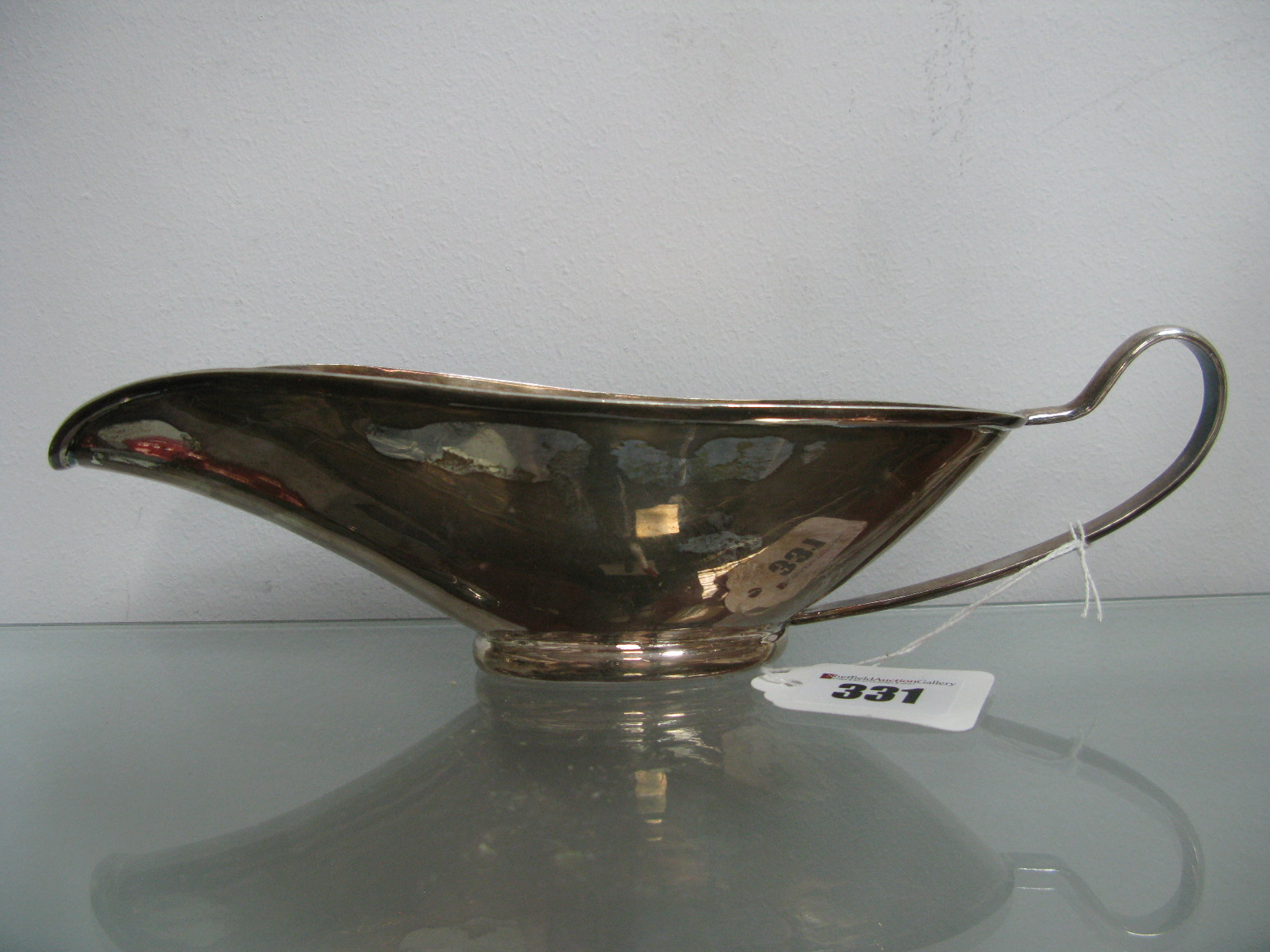 Lot 331 - A Modernist Style Sauce / Gravy Boat, of stylised elongated form, with loop handle, on oval rim