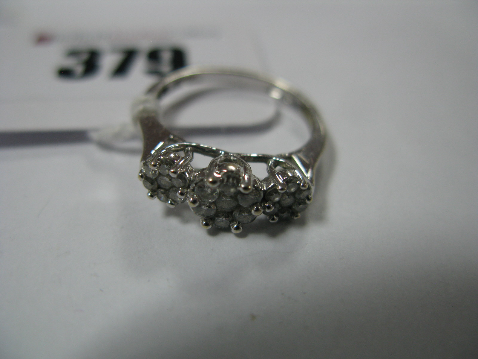 "Lot 379 - A Modern Diamond Set Cluster Style Dress Ring, claw set throughout, stamped ""18KT .50""."
