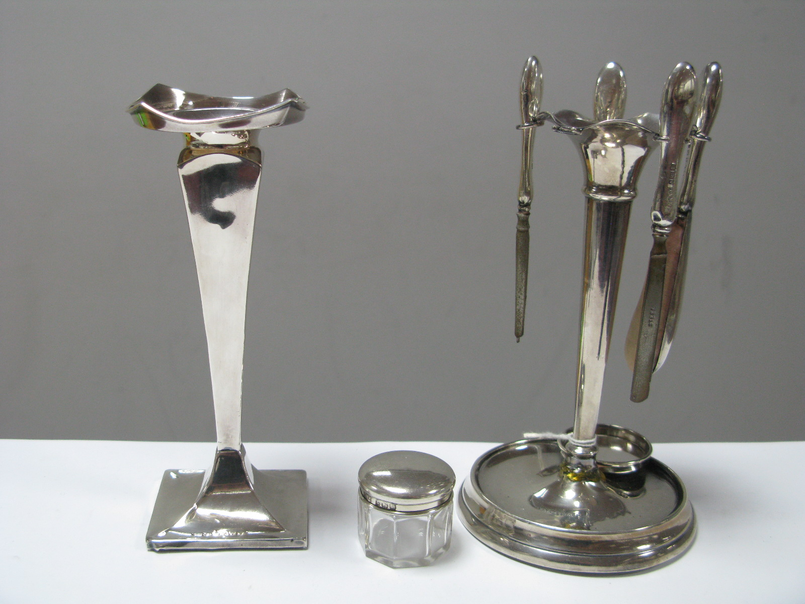 Lot 299 - A Hallmarked Silver Manicure Stand, together with a hallmarked silver vase, of tapering square form.