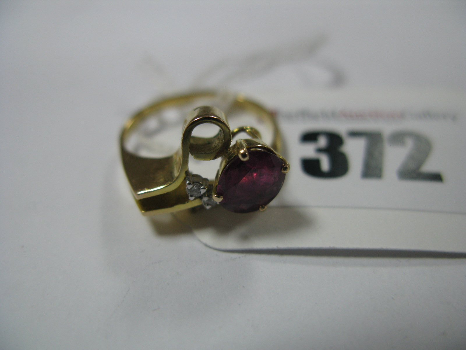 Lot 372 - A Ruby and Diamond Set Cocktail Dress Ring, of abstract design, oval four claw set within stylised