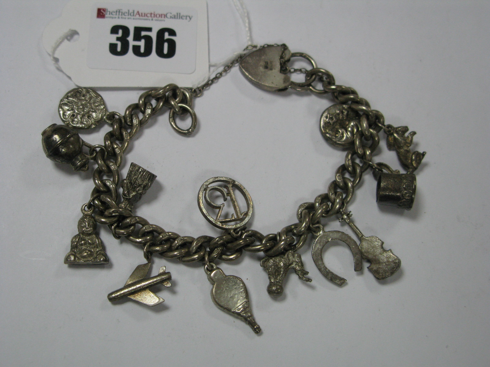 Lot 356 - A Hallmarked Silver Curb Link Bracelet, to heart shape padlock clasp, suspending numerous charm