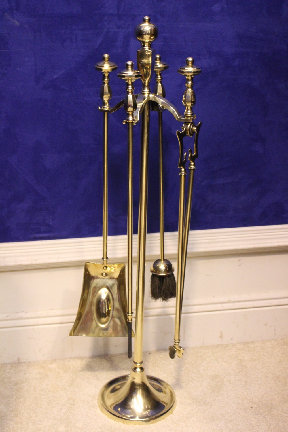 Lot 68 - A SET OF VICTORIAN BRASS FIRE IRONS on a stand, includes shovel, poker, tongs & brush, stand is