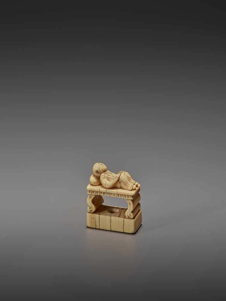 AN EARLY IVORY NETSUKE OF A CHINESE MAN SLEEPING ON AN OPIUM BED UnsignedJapan, early 18th - Image 2 of 11
