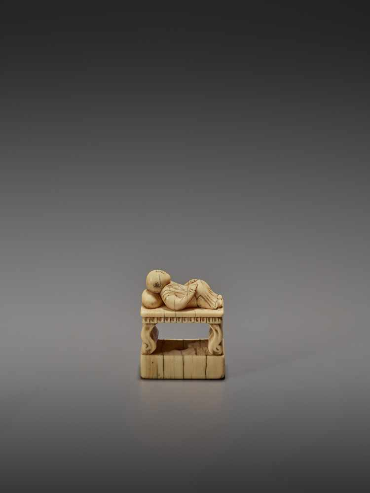 AN EARLY IVORY NETSUKE OF A CHINESE MAN SLEEPING ON AN OPIUM BED UnsignedJapan, early 18th - Image 4 of 11