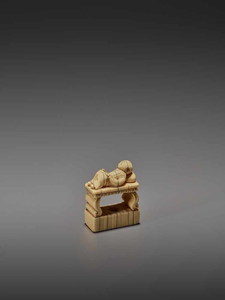 AN EARLY IVORY NETSUKE OF A CHINESE MAN SLEEPING ON AN OPIUM BED UnsignedJapan, early 18th - Image 5 of 11