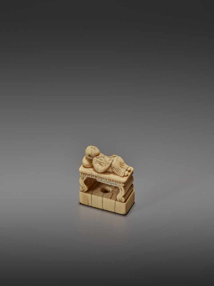 AN EARLY IVORY NETSUKE OF A CHINESE MAN SLEEPING ON AN OPIUM BED UnsignedJapan, early 18th