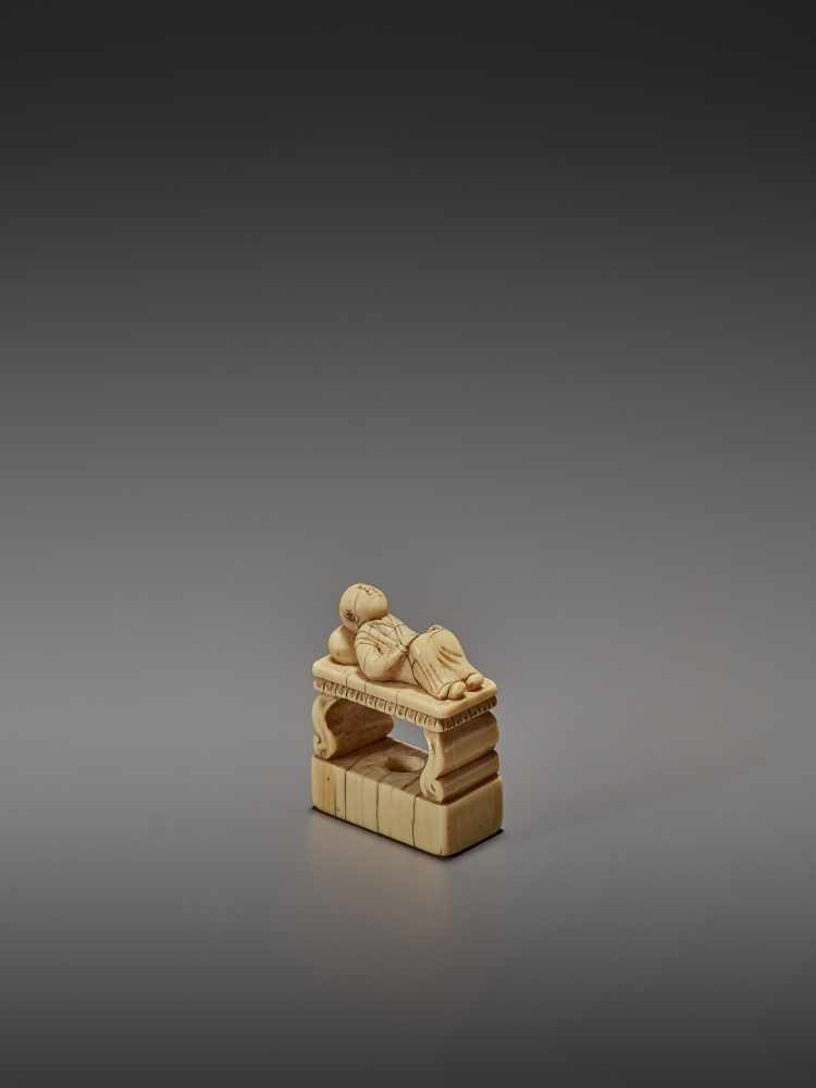 AN EARLY IVORY NETSUKE OF A CHINESE MAN SLEEPING ON AN OPIUM BED UnsignedJapan, early 18th - Image 3 of 11