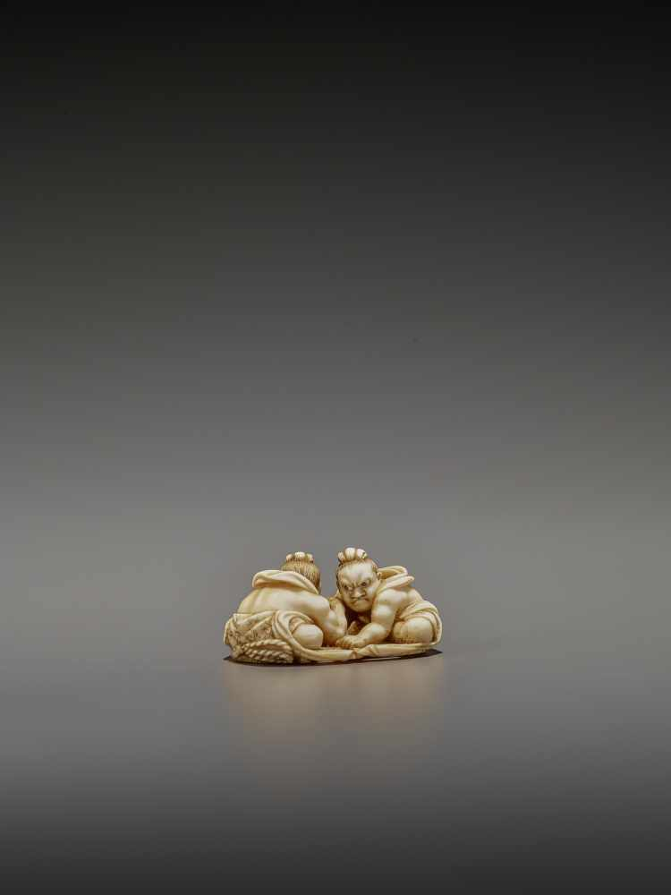 TOMOTAKA: AN IVORY NETSUKE OF TWO ARMWRESTLING NIO ON A WARAJI By Tomotaka, signed TomotakaJapan,